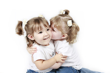 Adorable little twin girls kissing isolated on white background