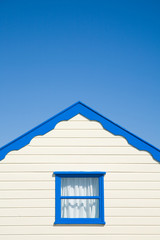 cream colored  beach huts with blue trim  under blue sky