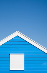 bright blue colored; beach hut with white trim; under blue sky