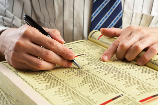 Businessman searching in yellow pages