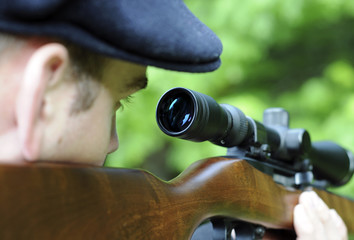 Man looking through scope on a rifle gun