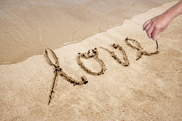 Love handwritten in sand for natural