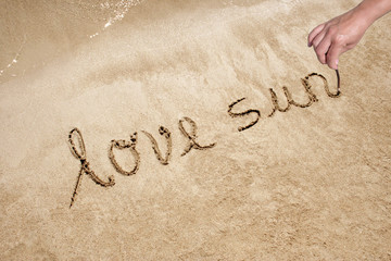 Love sun handwritten in sand on a a beach