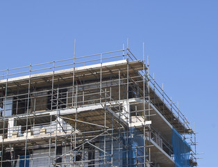 construction with scaffolding against blue sky
