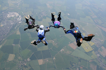 Skydivers in freefall holding hands