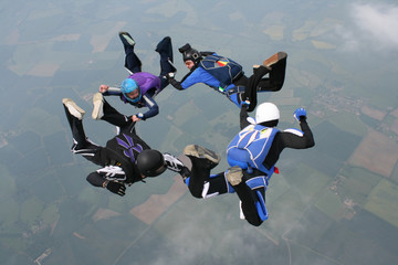 Four skydivers form a circle while in freefall
