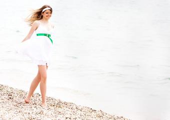 young happy girl walking on beach