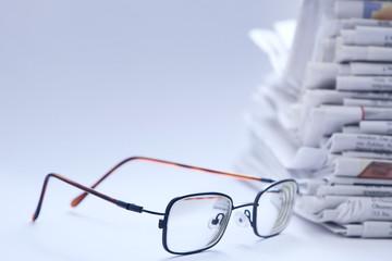 Brille vor Zeitungsstapel, Querformat