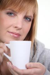 Portrait d'une femme blonde avec une tasse