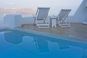 Swimming pool and deck chairs with sea view