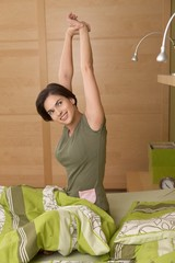 Smiling woman getting up stretching