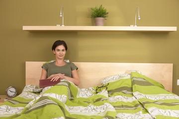 Portrait of smiling woman in bedroom