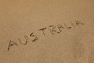 Australia drawn in the sand at the beach on an angle.