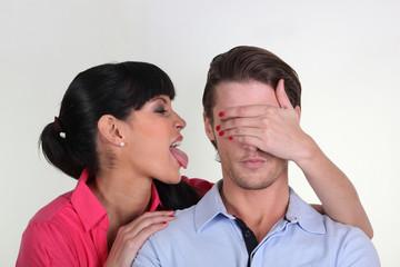 Jeune femme tirant la langue à un jeune homme
