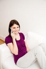 junge frau sitzt auf sofa und telefoniert, lacht
