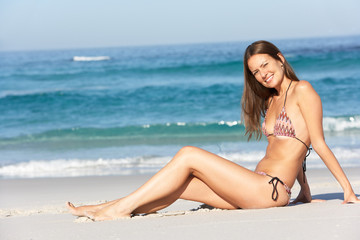 Young Woman Sitting On Sandy Beach On Holiday Wearing Bikini