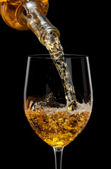 Fototapete - White wine poured in a glass isolated on a black  background