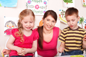 Children with teacher in play room.