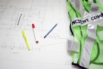 Green safety construction jacket , pens and drawing.