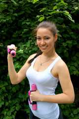 Woman with dumbbells in the park