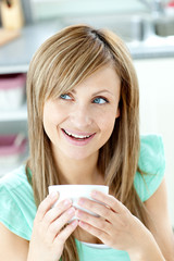 Portrait of a woman holding a cup of tea in the kitchen