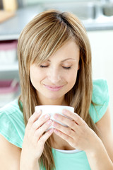 Delighted woman holding a cup of coffee in the kitchen