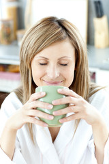 Delighted woman holding a cup a tea  in the kitchen