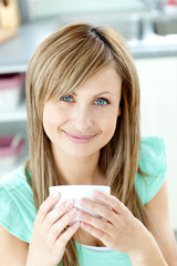 Confident woman holding a cup of coffee in the kitchen