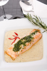 Cooked salmon fillets with  sauce on white plate