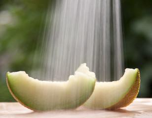 Fresh melon slices against green background