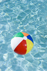 Colorful beach ball floating in swimming pool
