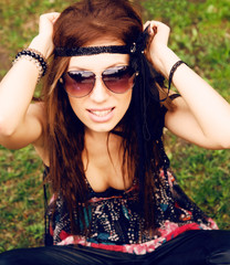 Beautiful young hippie girl sitting in the grass