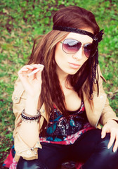 Beautiful young hippie girl sitting in the grass with cigarette