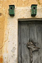 Two green nest boxes above an old door near the city of Vilafran