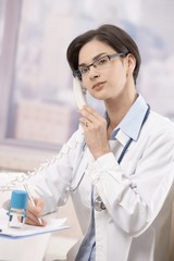 Young physician talking on phone