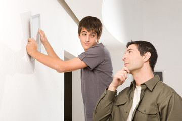 Teenager hanging a picture on the wall