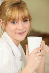 Portrait d'une jeune femme avec une tasse de café