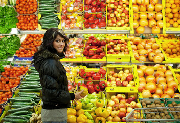 Beautiful young woman buying fruits and vegetables at a supermar