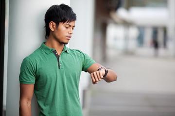 junger mann schaut auf die uhr