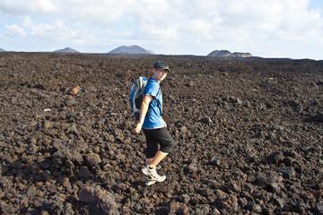 boy on walking trail thru volcanic area in Lanzarote