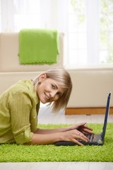Smiling woman with computer at home