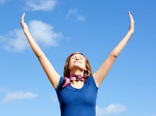 Jolly  blond woman punching tha air against blue sky