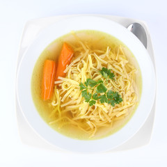 Chicken soup with macaroni and carrots and  a spoon