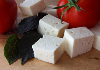 cheese and tomatoes on cutting board