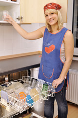 Junge Frau räumt Spülmaschine aus