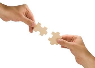 hands with pieces of puzzle on white background