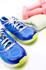 Sport shoes and weights isolated on white