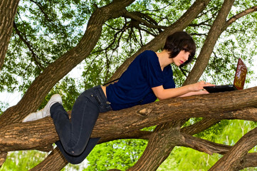 girl with notebook lying on branch