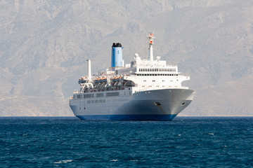 Tourist cruise sea liner is sailing in rocky bay