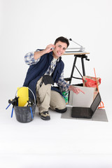 Tiler phoning in front of a laptop computer on white background